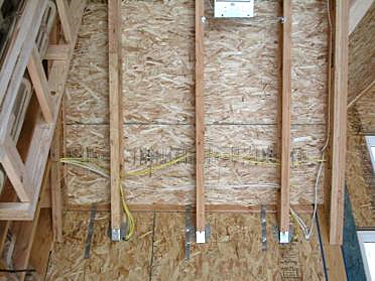 Example of SIPs used for wall and roof panels showing microlam and truss joist hanger connections and strapping, along with wiring